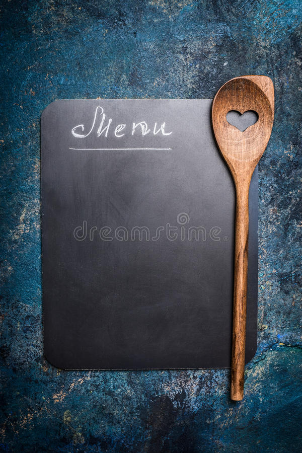 Menu background with chalkboard and cooking wooden spoon with heart, top view, place for text royalty free stock photography