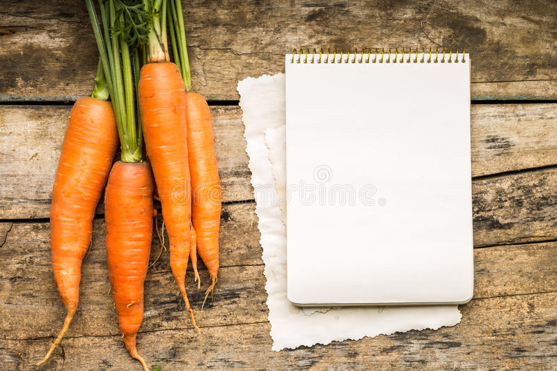 Menu background. Vegetables on table with cook book. Cooking with recipe book. Carrot royalty free stock image
