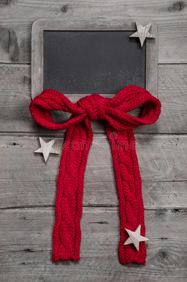 Menu board for christmas with red ribbon and stars on grey wooden background royalty free stock photos
