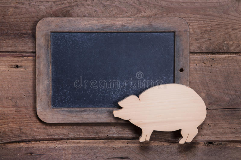Menu board with pink pig on wooden background for New Year. Sylvester, birthday or for a butcher - to say good luck royalty free stock images