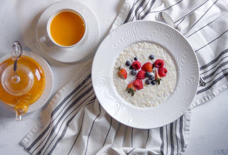 Menu at the cafe, Breakfast, Porridge with berries, Bulgur with coconut milk. Flatlay, Top view, Moody on black background,. Menu at the cafe, Breakfast stock photo