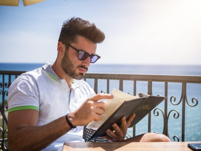 Menu da leitura do homem novo na barra exterior imagem de stock