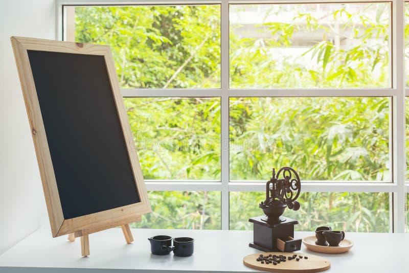 Menu de tableau noir sur le dessus de table en bois de brun foncé avec la tasse de coffe image libre de droits