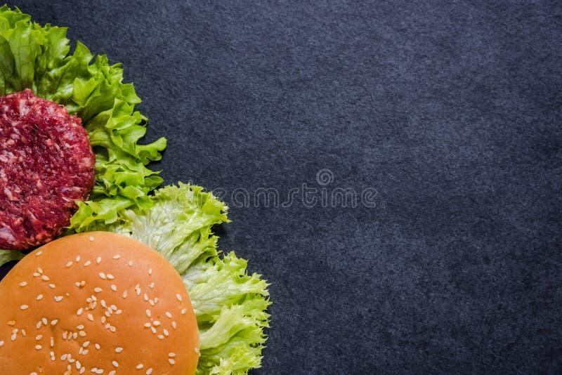 Menu del ristorante, ingredienti dell'hamburger e spazio scuri della copia immagine stock