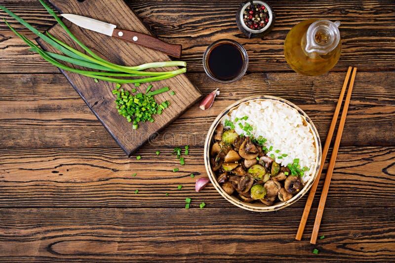 Menu del vegano alimento dietetico Riso bollito con i funghi ed i cavoletti di Bruxelles nello stile asiatico fotografia stock