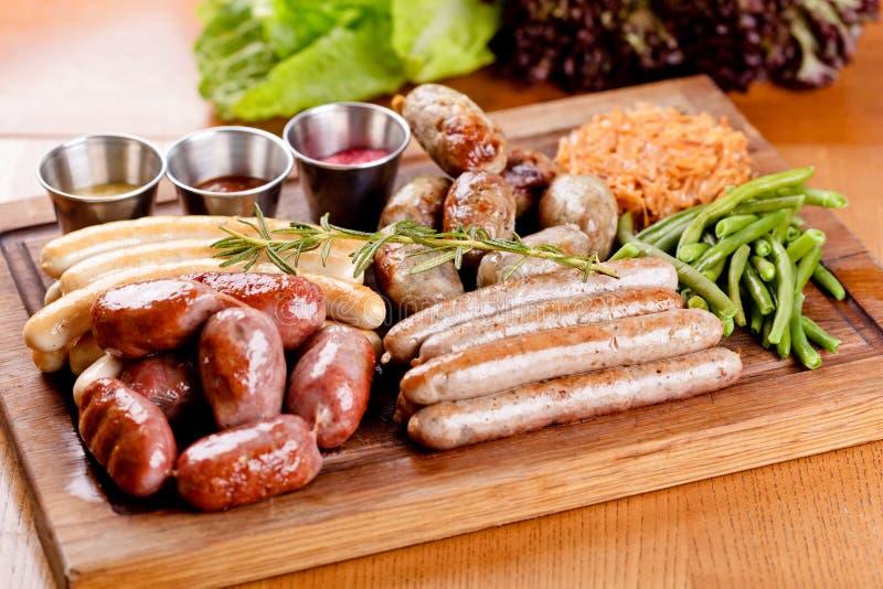 Menu dell'alimento di Oktoberfest Salsiccie arrostite assortite, crauti, fagiolini sul tagliere di legno fotografia stock libera da diritti