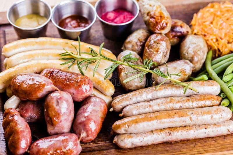 Menu dell'alimento di Oktoberfest Salsiccie arrostite assortite, crauti, fagiolini sul tagliere di legno immagini stock libere da diritti