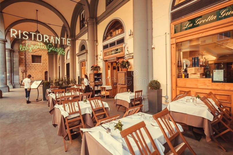 Menu della lettura della donna del ristorante tradizionale sotto gli arché della città antica della Toscana fotografia stock