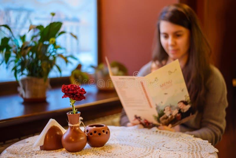 Menu della tenuta della donna mentre sieda in caffè fotografia stock libera da diritti