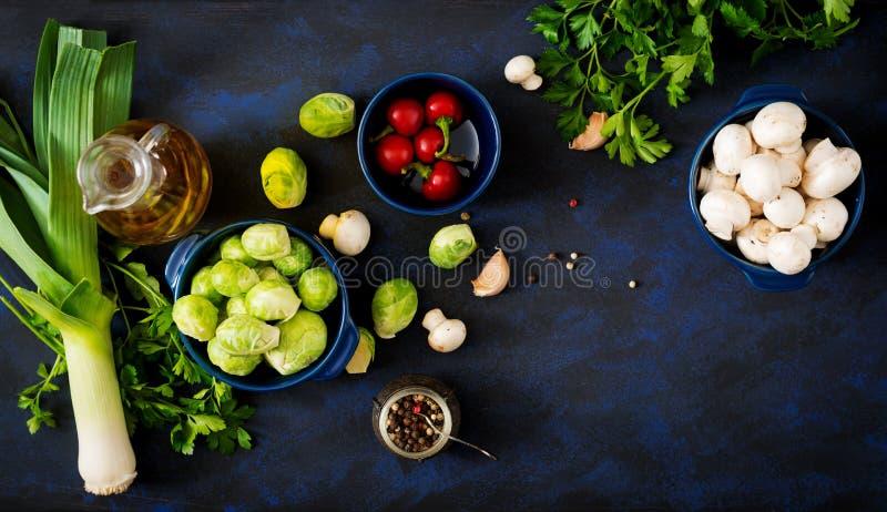 Menu dietético Ingredientes: Vegetais - couve-de-bruxelas, cogumelos, alho-porros e ervas em um fundo escuro foto de stock royalty free