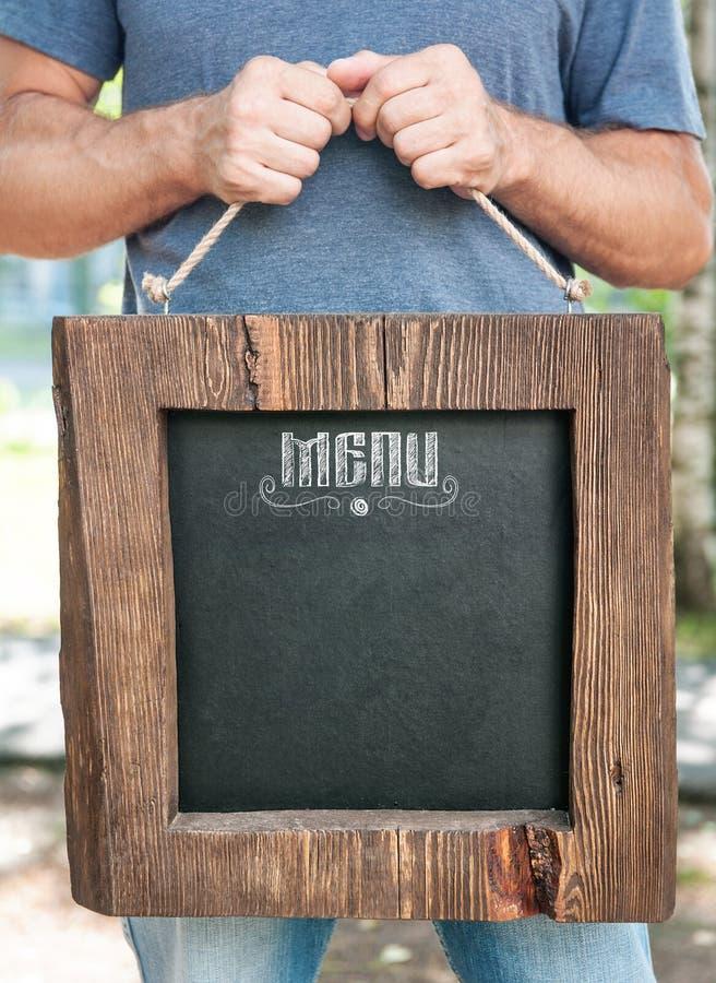 Menu do restaurante na posse da placa de madeira pela mão do homem Zombaria do molde imagens de stock royalty free
