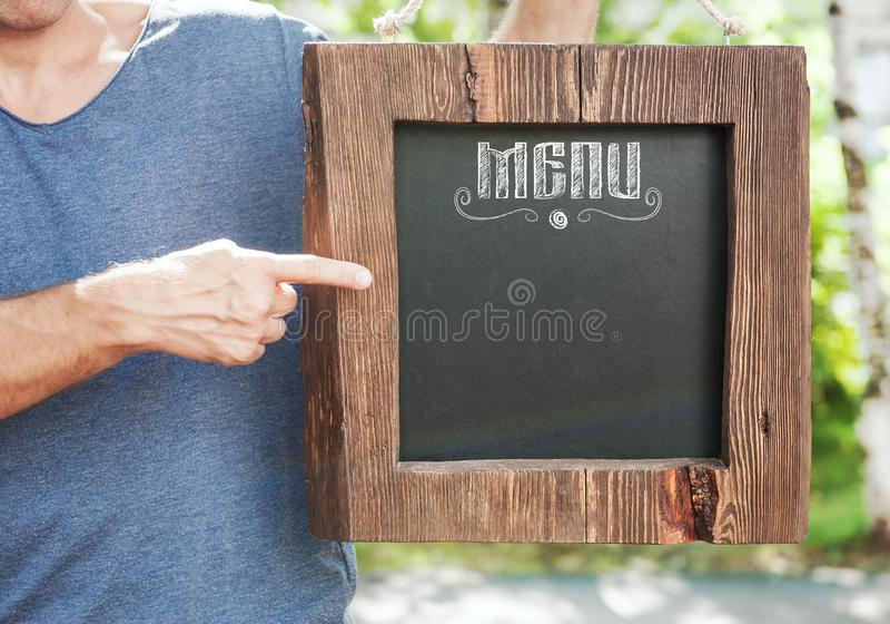 Menu do restaurante na posse da placa de madeira pela mão do homem Zombaria do molde foto de stock