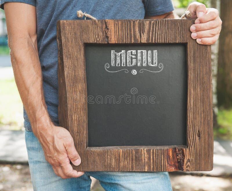 Menu do restaurante na posse da placa de madeira pela mão do homem Zombaria do molde fotos de stock
