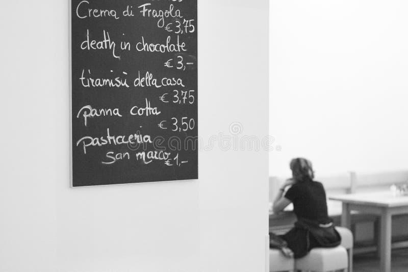 Menu em um café na parede com as mulheres que sentam-se em a fotos de stock