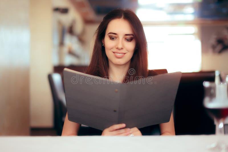 Menu fêmea da leitura do cliente em um restaurante fotos de stock
