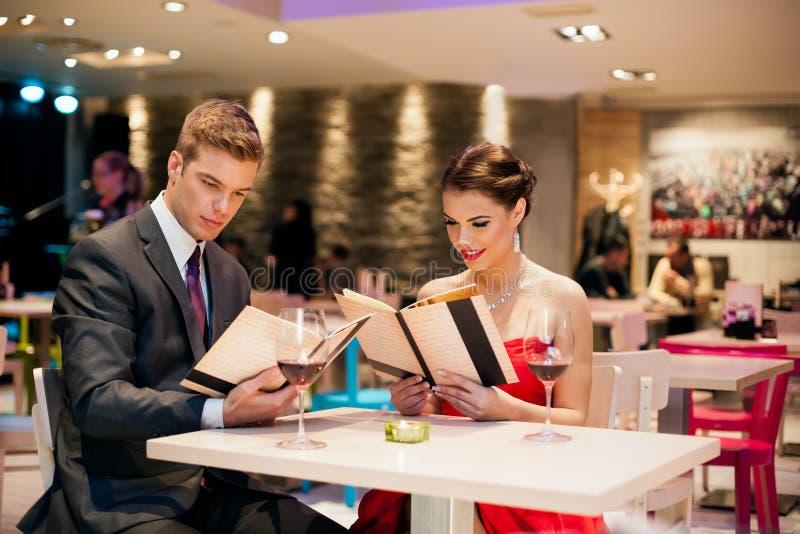 Menu feliz da leitura dos pares no restaurante fotografia de stock