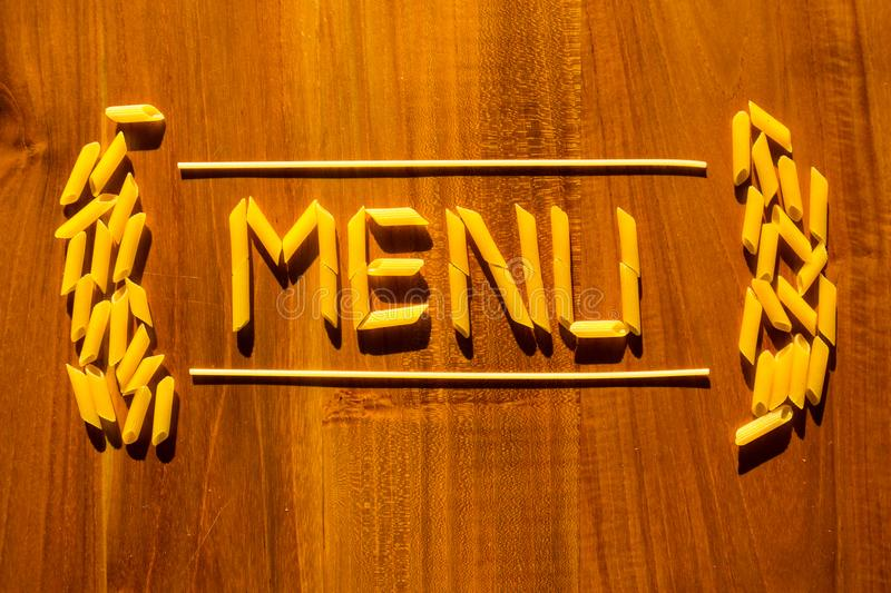 Menu lettering from penne and macaroni pasta on wooden table. Cooking restaurant concept royalty free stock images