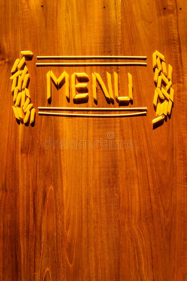 Menu lettering from penne and macaroni pasta on wooden table. Cooking restaurant concept stock image
