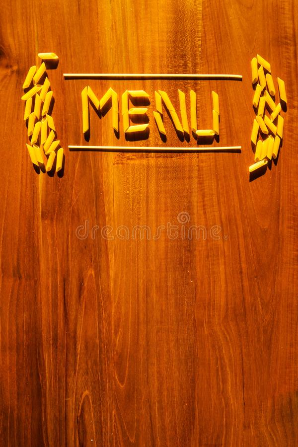 Menu lettering from penne and macaroni pasta on wooden table. Cooking restaurant concept royalty free stock photos