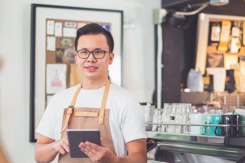 Menu masculin asiatique W de café de tablette de prise de tablier d'usage de barman images libres de droits