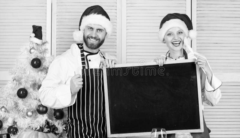 Menu for our family. Man and woman chef santa hat near christmas tree hold blackboard copy space. Christmas recipe royalty free stock image