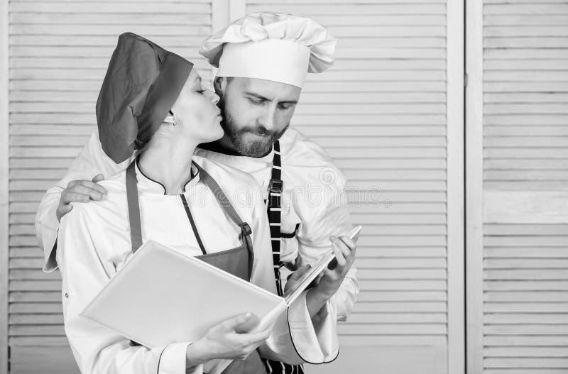 Menu planning culinaire keuken Geheim ingredi?nt door recept Eenvormige kok man en vrouwenchef-kok in restaurant Familie royalty-vrije stock foto