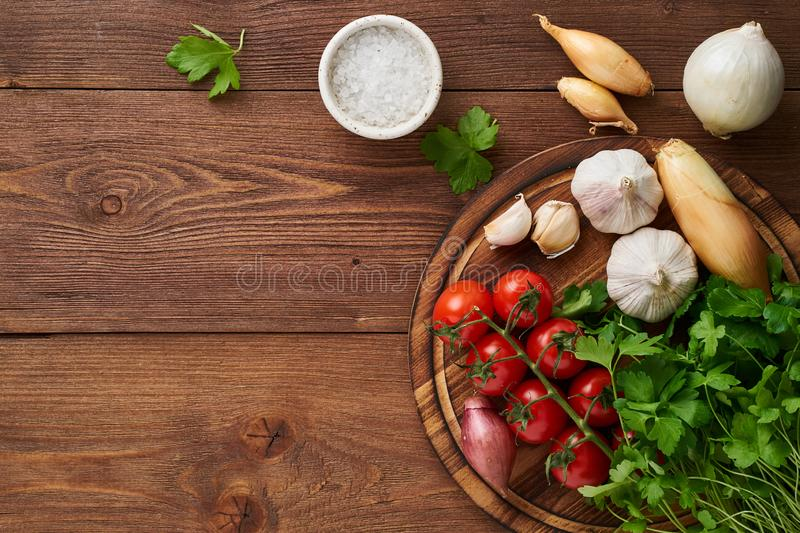 Menu, recipe, mock up, banner. Food seasoning background. Spices, Herbs and round wooden cutting board on brown dark wooden stock image