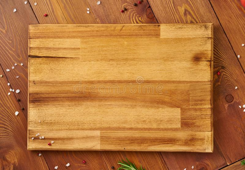 Menu, recipe, mock up, banner. Food seasoning background. Spices, Herbs and wooden cutting board on brown dark wooden backdrop. stock photography
