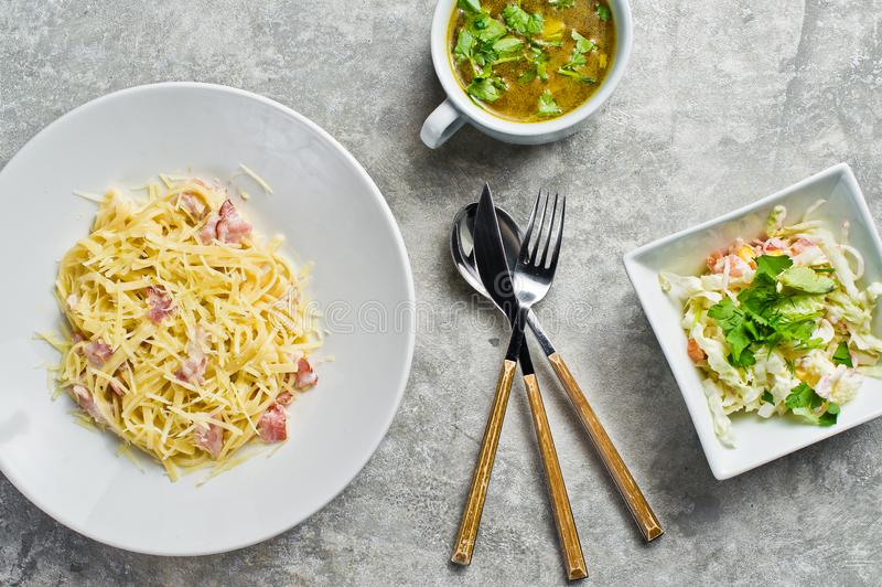 Meny f?r aff?rslunch, pasta Carbonara, gr?n sallad och feg soppa royaltyfria bilder