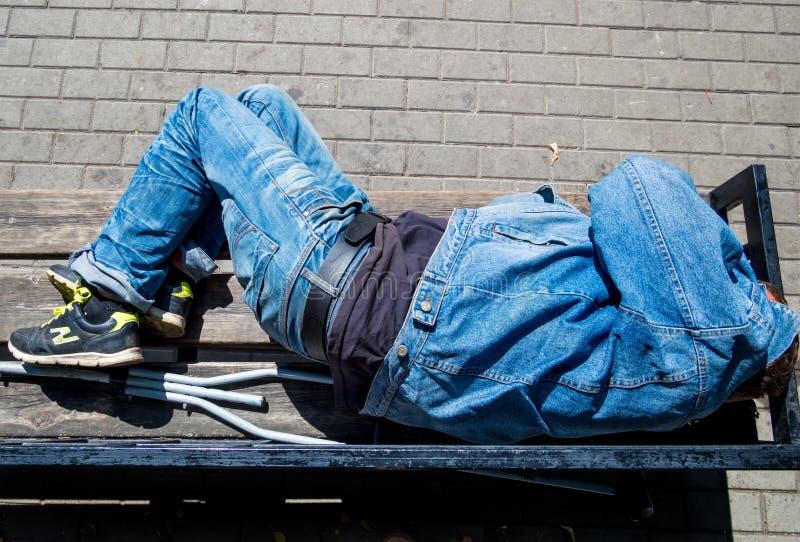 Menzogne addormentata dell'uomo su un banco fotografie stock libere da diritti