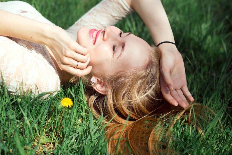 Menzogne bionda favorita sull'erba con i denti di leone Giovane risata adorabile sveglia di Girfriend in Sunny Day caldo fotografie stock libere da diritti