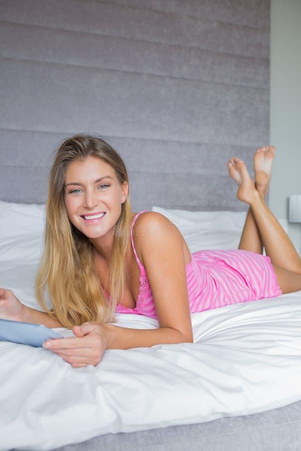 Menzogne bionda felice sul letto facendo uso della sua compressa digitale fotografia stock