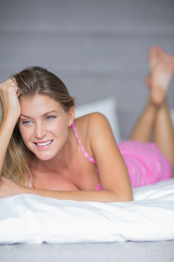 Menzogne bionda premurosa sul suo sorridere del letto fotografia stock libera da diritti
