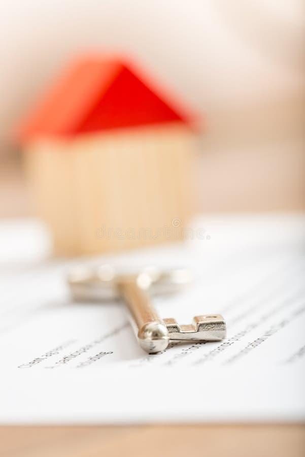 Menzogne chiave della casa d'argento su un contratto per l'acquisto fotografia stock