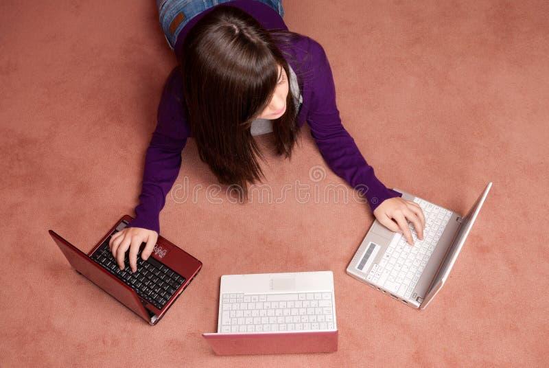 Menzogne del computer portatile di elaborazione multitask tre della giovane donna fotografia stock libera da diritti