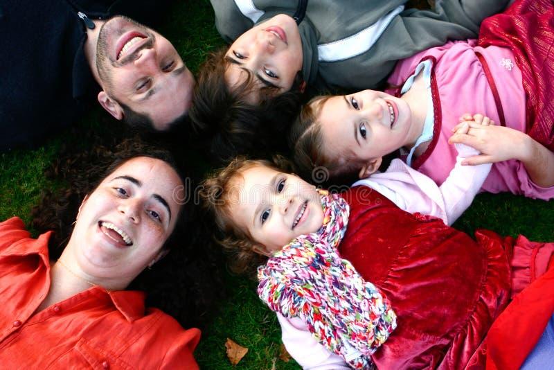 Menzogne della famiglia testa a testa su erba fotografie stock