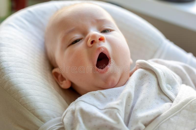 Menzogne di sbadiglio del neonato sveglio nella culla, in una nuova vita e nel fa immagine stock