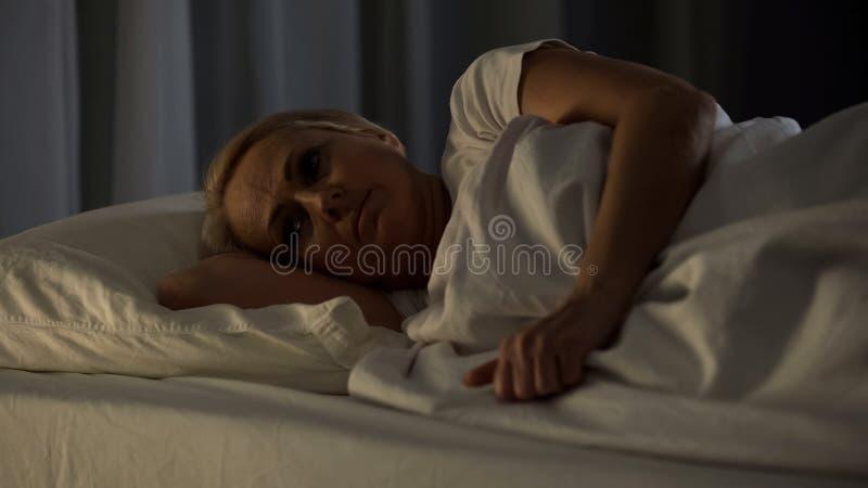 Menzogne paziente malato terminale nel letto di ospedale che soffre dal dolore e dall'insonnia fotografia stock