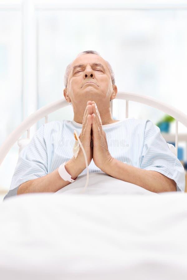 Menzogne paziente maschio nel letto di ospedale e pregare al dio immagine stock