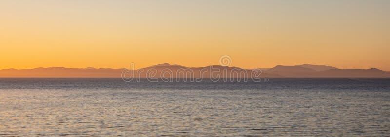 Mer Égée et collines d'Attica Greece, vue d'île de Kea au temps de coucher du soleil, fond clair de ciel, bannière images libres de droits