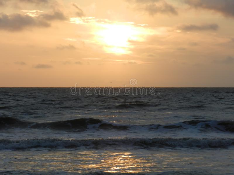 Mer avec des vagues dans un coucher du soleil jaune photographie stock libre de droits