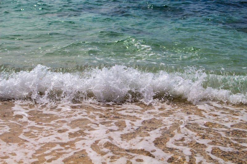 Mer avec la vague blanche éclaboussant au-dessus de la plage Mer de ondulation Eau de mer claire de bleu de turquoise au-dessus d photo libre de droits