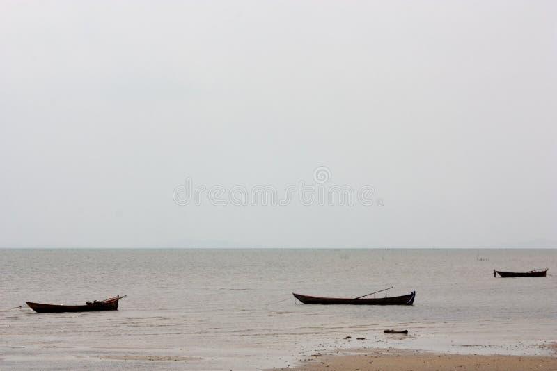 Mer calme avec trois longs canoës de pêche en eau peu profonde photographie stock libre de droits