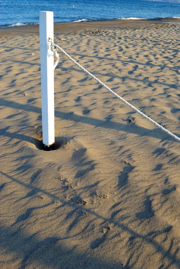 Mer d'été, borne blanche sur la plage photographie stock