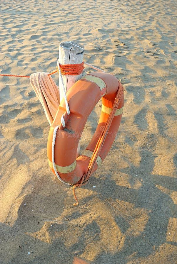 Mer d'été, bouée de sauvetage sur la borne blanche sur le sable, vertical images libres de droits
