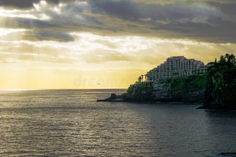 Mer d'or calme avec l'hôtel sur des falaises photos libres de droits