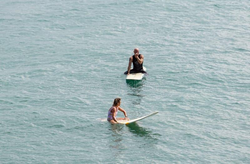 Mer de l'Italie Toscane le 18 juillet 2018 : Surfer sur le rivage du nord un couple attend la vague sur une planche de surf images libres de droits