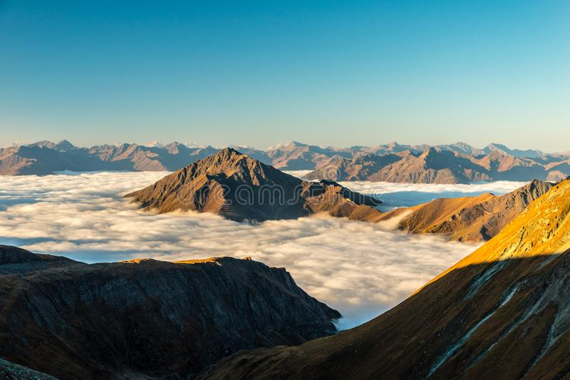 Mer de nuages flottant en vallée alpine dans le lever de soleil en automne, région de Grossglockner, Tyrol, Autriche photographie stock libre de droits