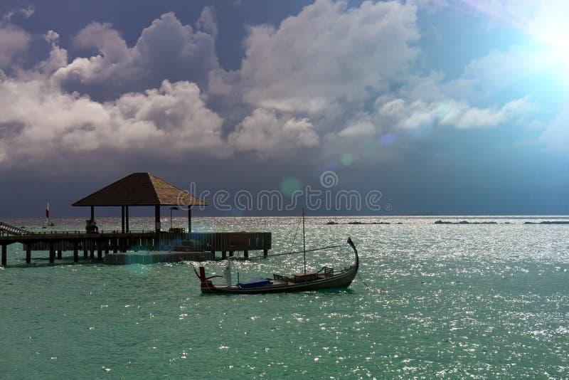 Mer et une silhouette de bateau sur l'eau maldives photographie stock libre de droits