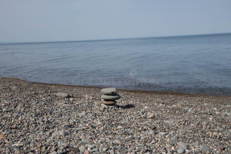 Mer Pebble Beach avec les pierres, vagues transparentes avec la mousse, un jour chaud d'été Plage de bardeau image stock